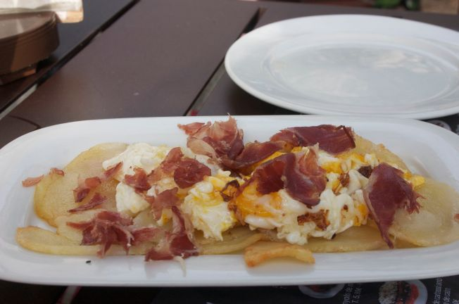 Thinly sliced fried potatoes topped with an egg and serrano ham